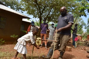 The Water Project: Shianda Community, Panyako Spring -  Mary Gets Assistance At The Tippy Tap