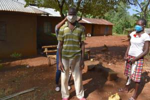The Water Project: Shianda Community, Panyako Spring -  Assiting Bernard To Fit His Mask