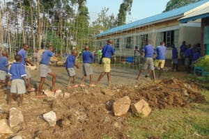The Water Project: Mwikhupo Primary School -  Students Help Place Wire Over Foundation