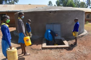The Water Project: Kitagwa Primary School -  Students Collecting Water From The Tank