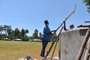 The Water Project: Kitagwa Primary School -  Field Officer Patience Hands Dorm Support Poles To Artisan Inside Tank