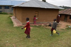 The Water Project: Kapkeruge Primary School -  Students Carrying Water From Home