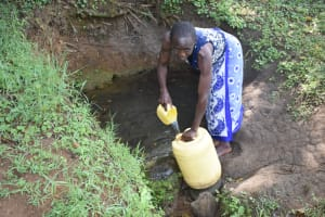 The Water Project: Emusaka Community, Manasses Spring -  Repha Collecting Water