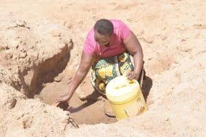 The Water Project: Kyamwalye Community -  Scooping Water