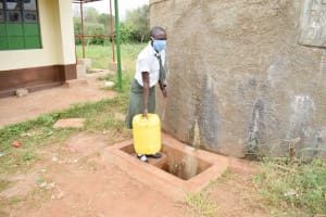 The Water Project: Nzoila Secondary School -  Student Fetching Water