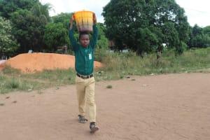 The Water Project: Kulafai Rashideen Primary School -  Student Carrying Water