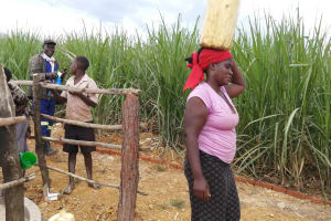The Water Project: Rubona Kyawendera Community -  Carrying Water From The New Well