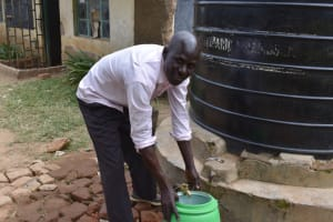 The Water Project: Tande Primary School -  Mr Kituyi Fetches Water From The Tank