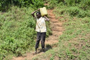 The Water Project: Emutetemo Community, Lubale Spring -  Community Member Carrying Materials To Spring Site