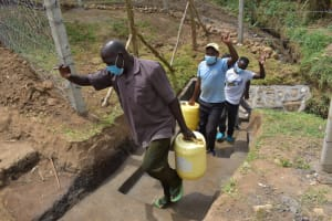 The Water Project: Mukoko Community, Zebedayo Mutsotsi Spring -  Men Carrying Their Fetched Water Home