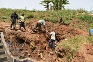 The Water Project: Mushikulu B Community, Olando Spring -  Backfilling With Large Rocks