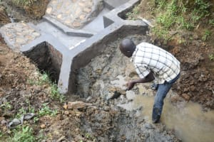 The Water Project: Emutetemo Community, Lubale Spring -  Reinforcing The Headwall With Clay For Better Water Collection