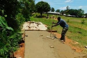 The Water Project: Ibokolo Primary School -  Pouring Concrete Latrine Foundation