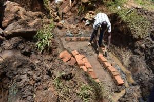 The Water Project: Mushikulu B Community, Olando Spring -  Bricksetting