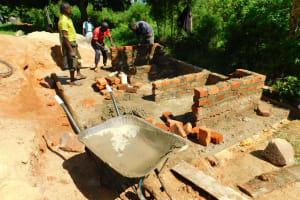 The Water Project: Ibokolo Primary School -  Raising Latrine Walls