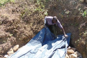 The Water Project: Elwichi Community, Mulunda Spring -  Backfilling With Tarp