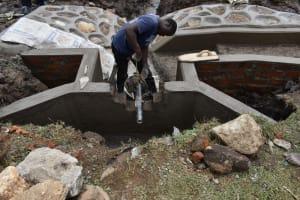 The Water Project: Isanjiro Community, Musambai Spring -  Pipe Setting