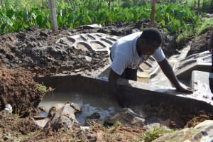The Water Project: Isanjiro Community, Musambai Spring -  Backfilling With Clay And Stones