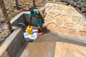 The Water Project: Isanjiro Community, Musambai Spring -  Mercy Collecting Water