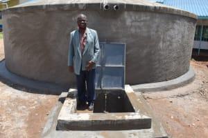 The Water Project: Gidimo Primary School -  Teacher Tom Nyambetsa At The Rain Tank