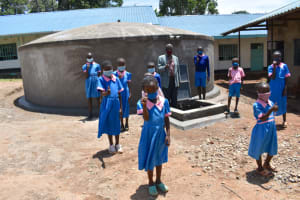 The Water Project: Gidimo Primary School -  Children And Teacher Gives Thumbs Up At The Rain Tank