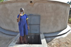 The Water Project: Jimarani Primary School -  A Girl Holding Up A Glass Of Water