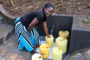 The Water Project: Emutetemo Community, Lubale Spring -  Selpher Keya Shiundu Fetching Water