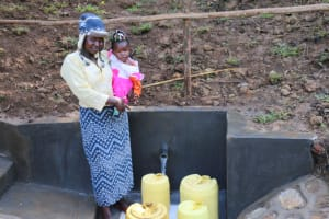 The Water Project: Emutetemo Community, Lubale Spring -  A Mother With Her Baby At The Spring