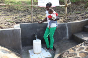 The Water Project: Mabanga Community, Ashuma Spring -  Fetching Water With Her Baby