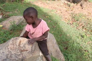 The Water Project: Khunyiri Community, Edward Spring -  A Child Playing On A Rock