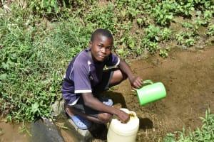 The Water Project: Emuyere Community, Kaikai Spring -  Joseph Fetching Water
