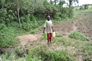 The Water Project: Emuyere Community, Kaikai Spring -  Man Carrying Water