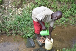The Water Project: Emuyere Community, Kaikai Spring -  Man Fetching Water