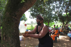 The Water Project: Lungi, Suctarr, #47 Kamara Street -  Community Member Demonstrates Using The Tippy Tap