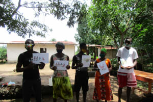 The Water Project: Lungi, Suctarr, #47 Kamara Street -  Community Members Hold Posters