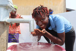 The Water Project: Lungi, Tintafor, Police Barracks E-Line Block 7 -  Young Woman Drinking From The Well