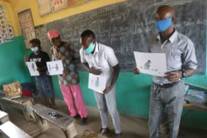 The Water Project: Lungi, Tintafor, Sierra Leone Church Primary School -  Teachers Hold Up Training Posters