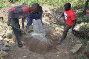 The Water Project: Litinye Community, Vuyanzi Spring -  Community Members Help Mix Cement