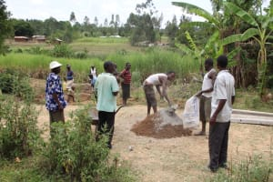 The Water Project: Mayuge Community, Ucheka Spring -  Community Members Help Mix Cement