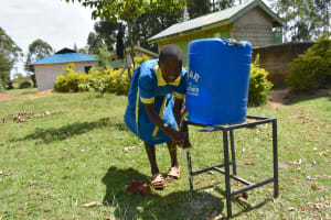 The Water Project: Shikomoli Primary School -  Pupil Happily Washing Hands