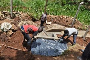 The Water Project: Shamoni Community, Shatuma Spring -  Backfilling With Plastic Sheet