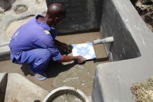 The Water Project: Litinye Community, Vuyanzi Spring -  Tile Setting