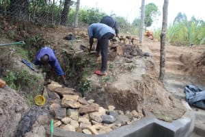 The Water Project: Litinye Community, Vuyanzi Spring -  Backfilling With Stones