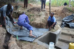 The Water Project: Litinye Community, Vuyanzi Spring -  Backfilling With Polythene