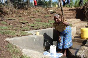 The Water Project: Litinye Community, Vuyanzi Spring -  An Elderly Woman Fetches Clean Water