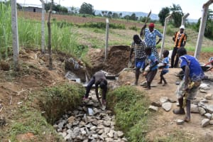 The Water Project: Wepika Community, Musa Mmasi Shikwe Spring -  Backfilling With Large Rocks