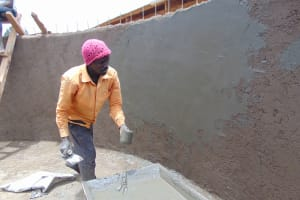 The Water Project: Saosi Primary School -  Applying A Thin Layer Of Cement Coat