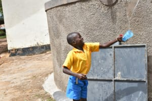 The Water Project: Shikomoli Primary School -  Student Celebrating At Water Tank