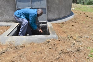 The Water Project: Isikhi Primary School -  A Teacher Making Use Of The Rain Tank