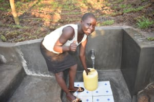 The Water Project: Khaunga A Community, Murutu Spring -  Thumbs Up While Collecting Water